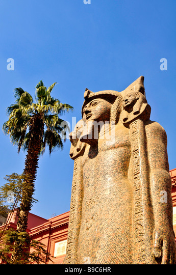 Cairo Museum Egypt ancient Egyptian sculpture statue outdoors with palm tree and blue sky - Stock Image