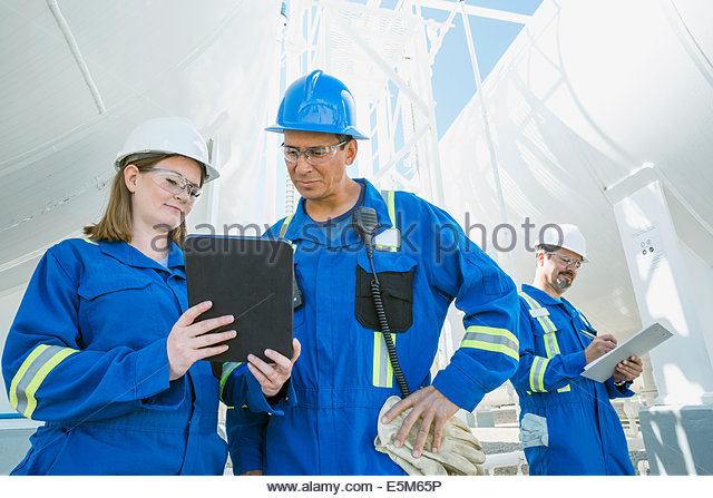 Workers using digital tablet at gas plant - Stock Image