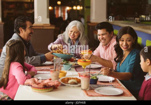 Family enjoying dinner in restaurant - Stock Image
