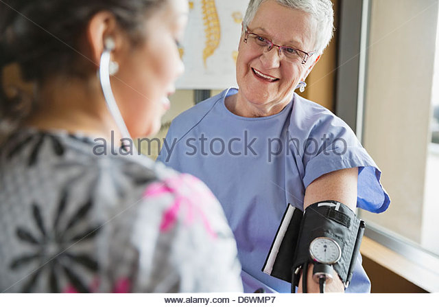 Young female nurse checking patient's blood pressure in clinic - Stock Image