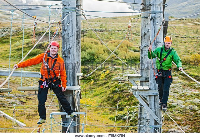 Men balancing at high rope access course, Iceland - Stock-Bilder