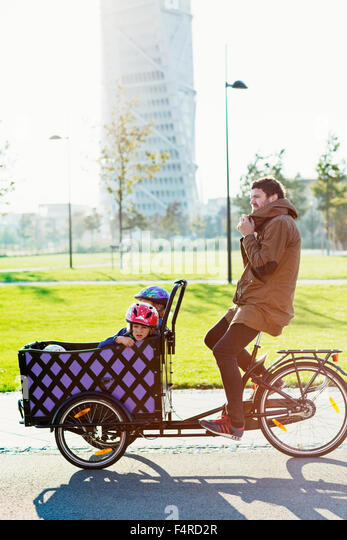 Sweden, Skane, Malmo, Vastra Hamnen, Father driving sons (4-5 and 6-7) in freight tricycle in urban park - Stock Image