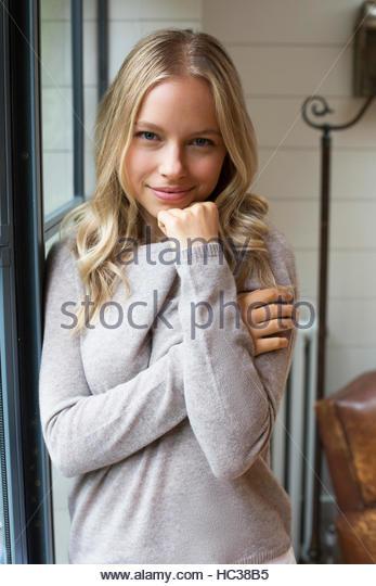 Young woman standing beside window. - Stock Image