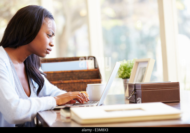 Woman Using Laptop On Desk At Home - Stock Image