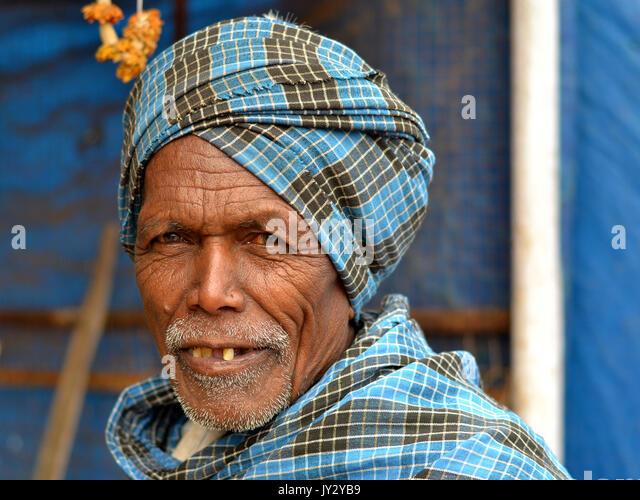 Closeup street portrait of an old Indian Adivasi man, wearing a blue-checkered turban. - Stock Image