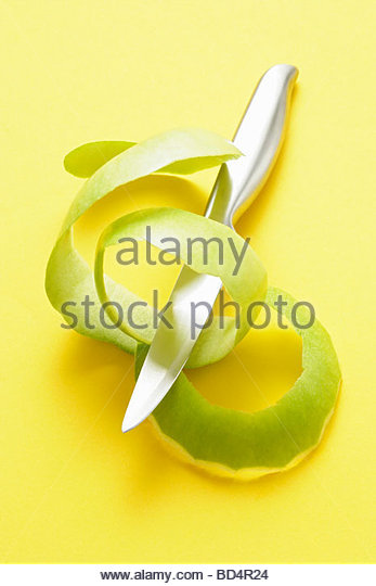 Green apple peel with knife - Stock Image