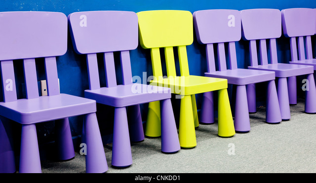 A yellow colored one in the middle of several purple colored chairs for children - Stock Image