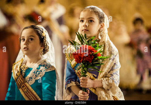 Valencia, Spain. March 18th, 2014: A little Fallera finally offers her flower bouquet to the Virgin and hands it - Stock Image
