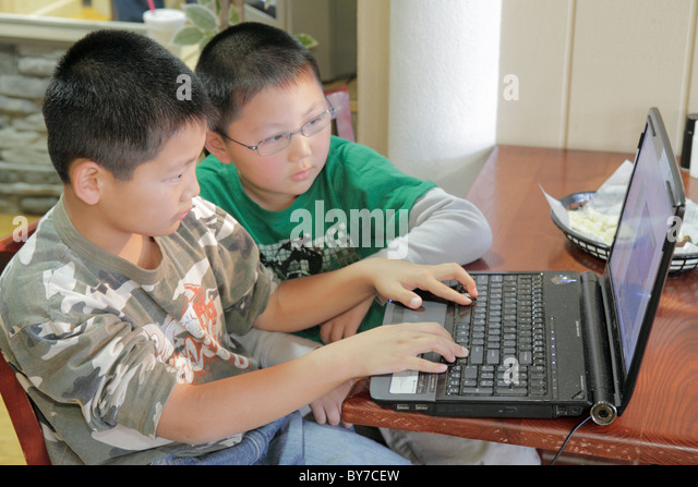 Georgia Gainesville Asian boy brother sibling child student laptop computer technology skills development sharing - Stock Image