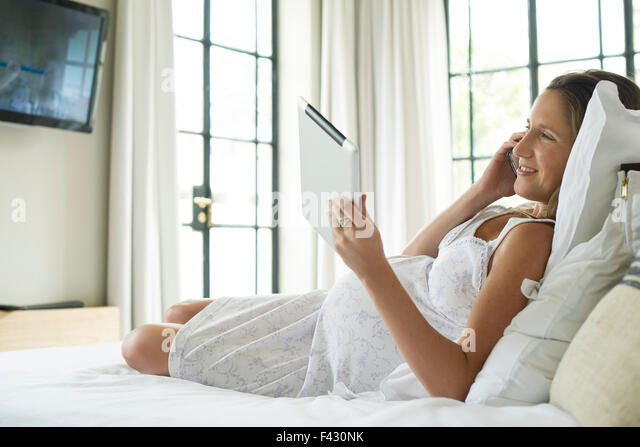Pregnant woman relaxing in bed, using digital tablet and chatting on cell phone - Stock Image