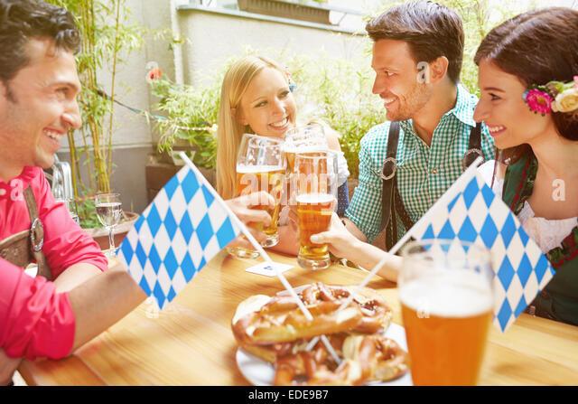 Happy friends in bavarian beer garden drinking beer in summer - Stock Image