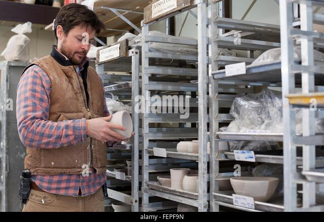 Potter in storage room quality checking unfinished clay pots - Stock Image