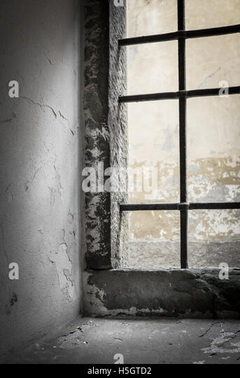 Contrasting light shines through the window of abandoned house. Shallow DOF. - Stock Image