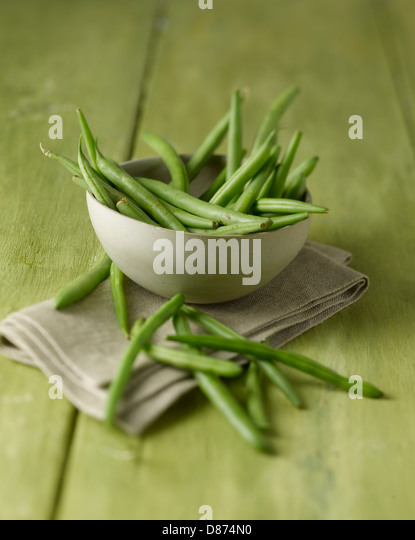 Bowl of green beans on wooden table, close up - Stock Image