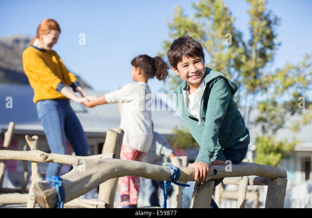 Teacher and students playing outdoors - Stock Image