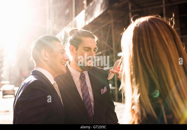 Businesswoman showing smart phone to friends on sunny day - Stock-Bilder