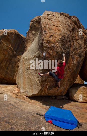 Caucasian male climber on a highball boulder in Hampi, India. - Stock-Bilder