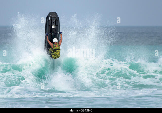 Spectacular acrobatic action provided by competitors at the IFWA jetski championship at  Fistral, Newquay in Cornwall. - Stock-Bilder