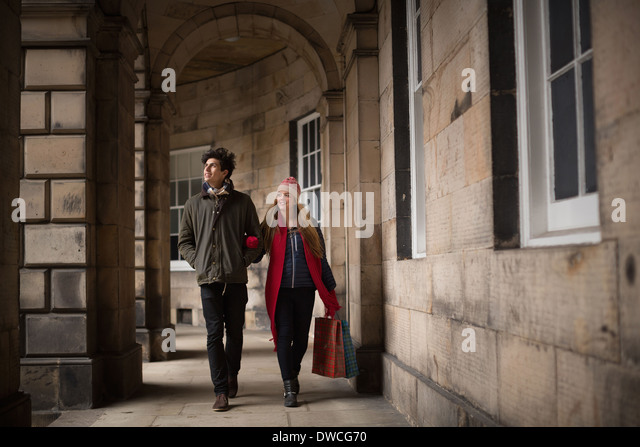 A young couple walk in the centre of Edinburgh - Stock Image