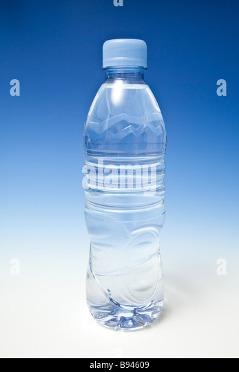 Bottled water on a graduated blue studio background - Stock Image