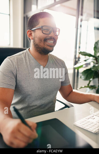 Happy graphic designer working in his own office. He is using digitized graphic tablet and digital pen for editing. - Stock Image