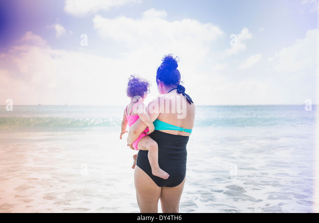 Rear view of mother and daughter looking out to sea - Stock-Bilder