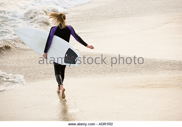 Female surfer running to the sea - Stock Image