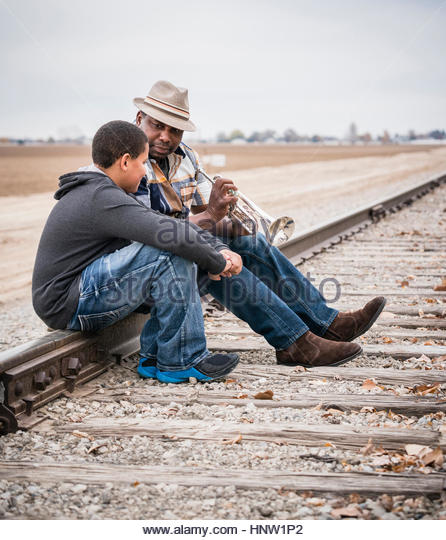 Father and son sitting on train track with trumpet - Stock-Bilder