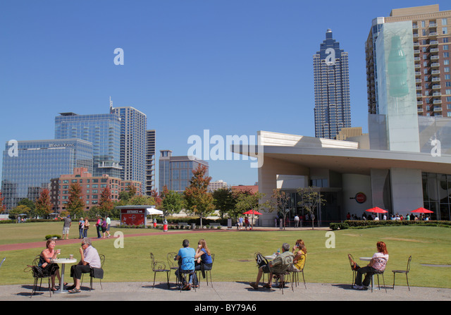 Atlanta Georgia Pemberton Place World of Coca-Cola downtown skyline building lawn outdoor tables cafe man woman - Stock Image