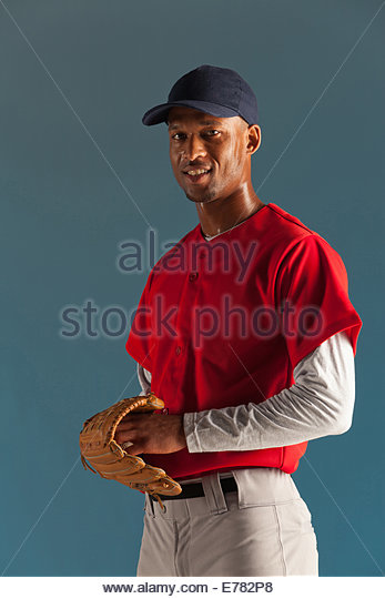Baseball player holding ball and glove - Stock Image