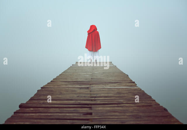 Red hooded woman looks at foggy lake on a wooden pier . Sadness and loneliness concept - Stock-Bilder