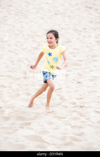 Girl Running on Beach - Stock Image