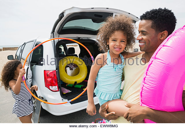 Portrait of father and daughter arriving at beach - Stock Image