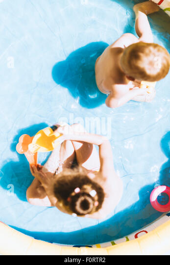 Young children playing with toys inside an inflatable pool during summertime - Stock Image