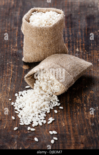 Raw white rice in burlap bag - Stock Image