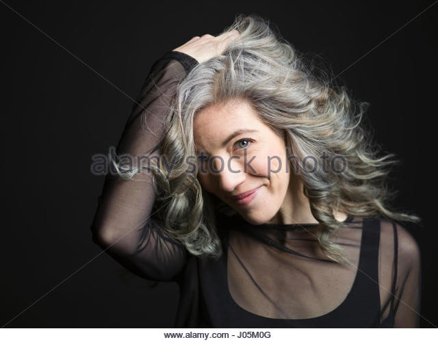 Portrait confident woman with hand in gray hair against black background - Stock Image