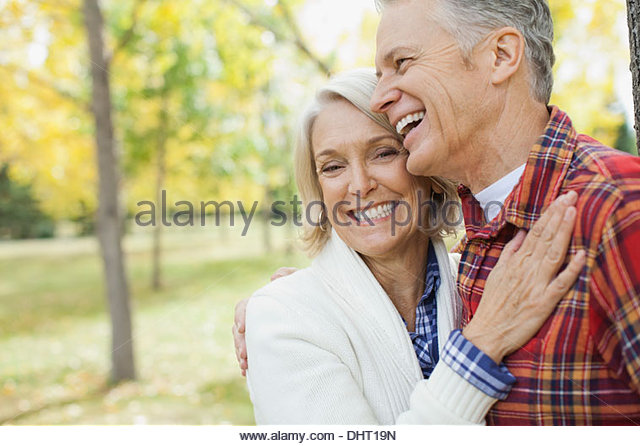 Portrait of happy mature woman with man at park during autumn - Stock Image
