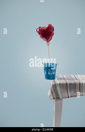 a heart shaped balloon balanced on the edge of a table - Stock Image