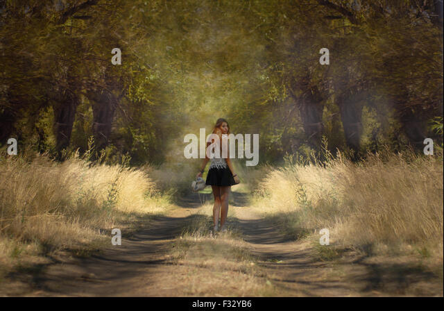 Tall girl walking trouhgt the forest looking back - Stock Image
