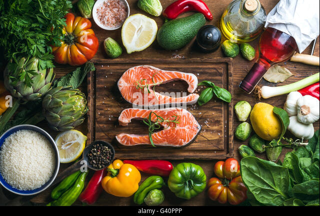 Raw uncooked salmon steak with vegetables, rice, herbs, spices and wine bottle on chopping board over rustic wooden - Stock Image