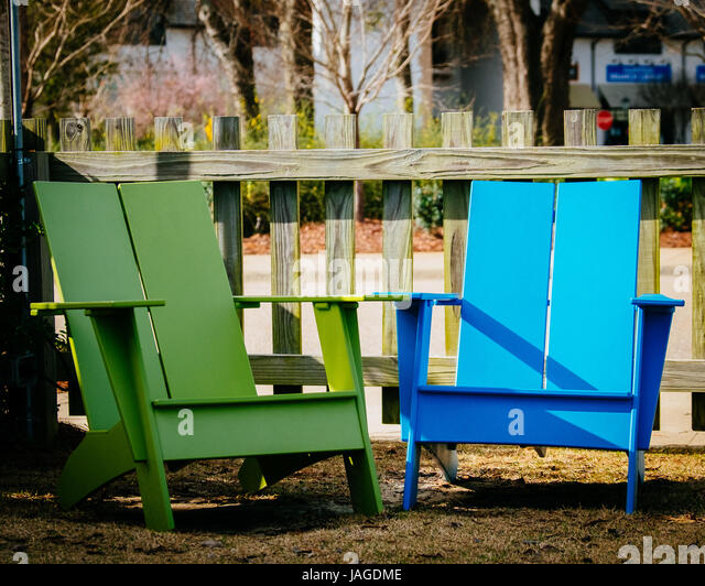 Two brightly colored, blue and green, adirondack chairs in an outdoor setting. - Stock Image