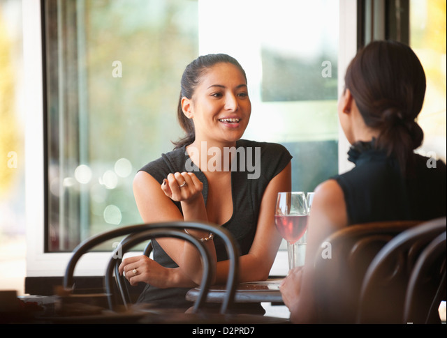 Asian friends sitting together in cafe - Stock Image
