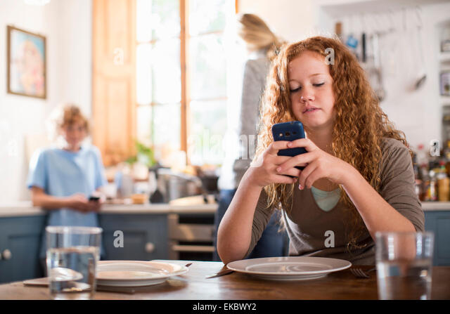 Teenage girl using smartphone at dining table - Stock-Bilder