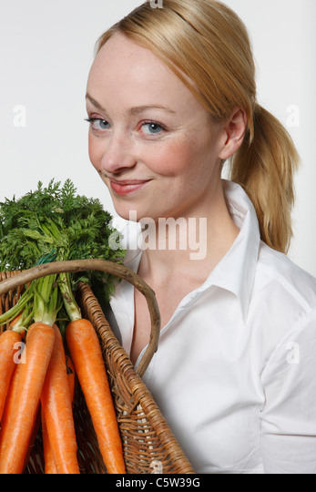 Young woman holding bunch of carrots, portrait - Stock Image