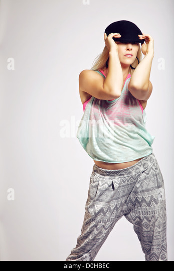 Portrait of a fashionable teen with trendy outfit posing against gray background - Stock-Bilder