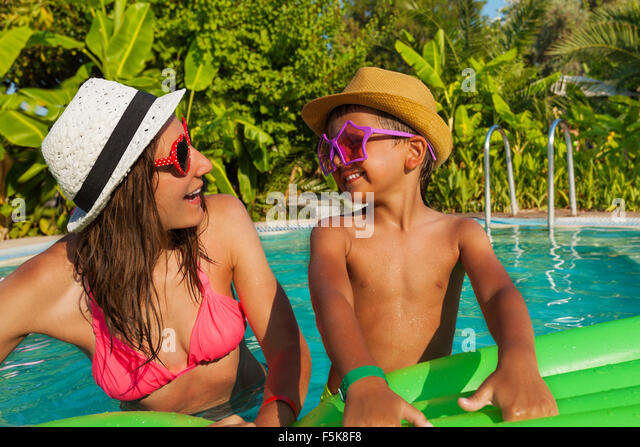 Happy mom and her son wearing sunglasses in pool - Stock Image