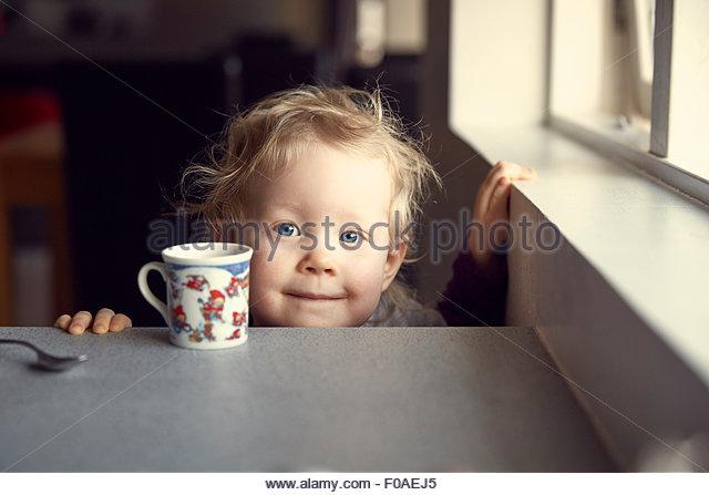 Portrait of female toddler peering from kitchen breakfast bar - Stock Image