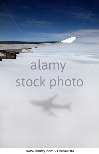 Jumbo jet, Boeing 747 in mid-air, view at clouds shadow of the airplane - Stock Image