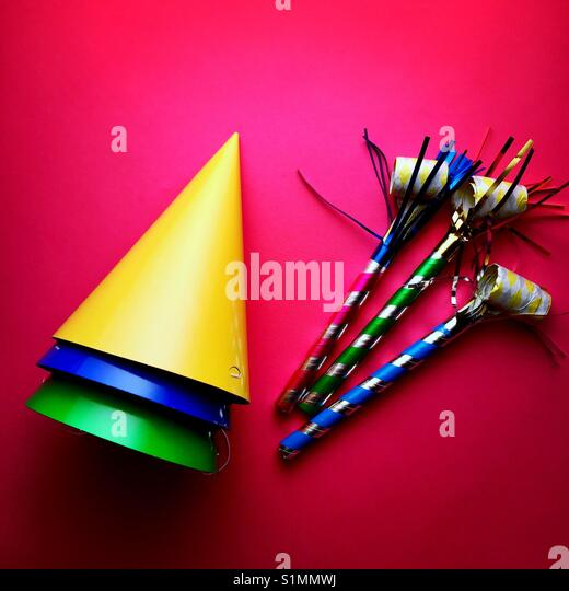 A bright colourful shot of party hats and noise makers - Stock Image