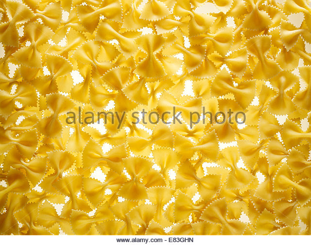 Uncooked Bow tie or Farfalle Pasta as texture background - Stock Image